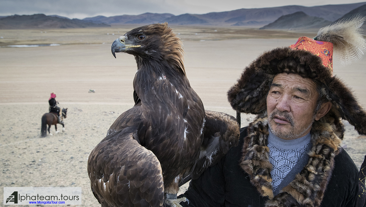 An eagle hunter with his eagle on the mountain